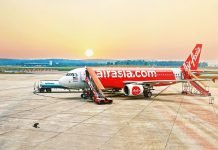 Red AirAsia Plane on a Runway at Sunset