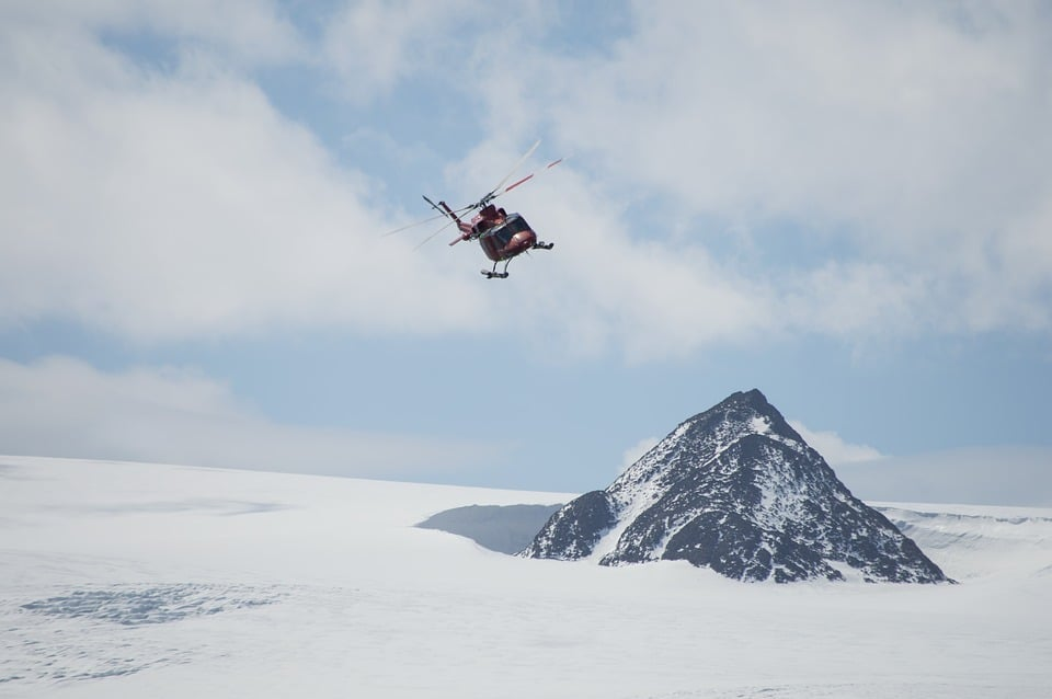 Helicopter Flying Over Thin Snow at Antarctica