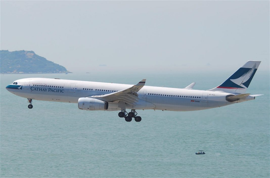 Plane of Cathay Pacific Flying Over the Ocean